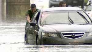 Two men push a stalled car through a flooded street Saturday in the Chicago, Illinois, area.