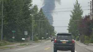Smoke from a cargo plane crash in Alaska rises through the trees.