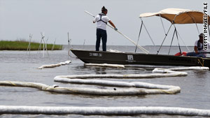 A worker adjusts an oil boom last month near Pointe Aux Chenes, Louisiana.