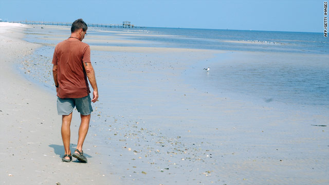 Though the beach has been cleaned up, Clarence Barthel walks alone at Pass Christian, Mississippi, on August 4.