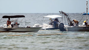 Crews soak up oil residue from the Gulf of Mexico oil spill in June in Orange Beach, Alabama.
