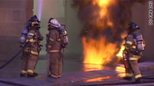 A firefighter hoses down a building as flames shoot through a sidewalk on F Street in Washington.