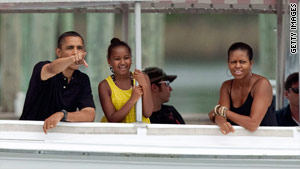 President Obama, with daughter Sasha and the first lady, watch porpoises off Panama City Beach on Sunday.