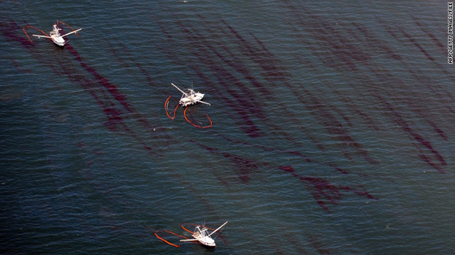 Fishing boats drag booms through oil near a Louisiana barrier island on May 7, two weeks after the Deepwater Horizon sank.