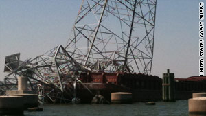 A high voltage tower learns over Texas' Houston Ship Channel on Monday, a day after a tow vessel hit it.