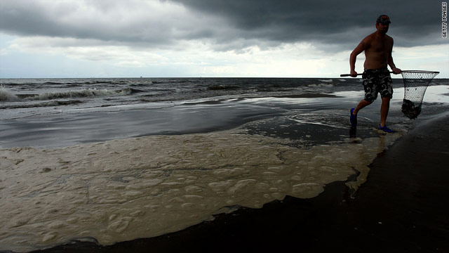 Ricky Breaux wades in from the ocean near a pool of dispersed oil on a Louisiana reopened beach in August.