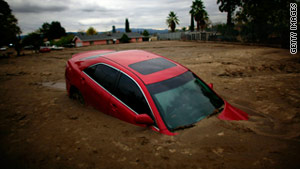 A car is buried in mud after flooding this week in Highland, California.