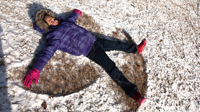 Ariana Ingle, 6, makes a snow angel in a dusting of white Friday at Piedmont Park in Atlanta, Georgia.