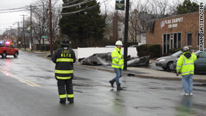 Crews deal with wind damage on Long Island, New York, on Sunday. About 150,000 customers are without electricity there.