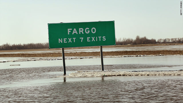 Floodwaters surround a sign Sunday along Interstate 29 marking exits to Fargo, North Dakota.