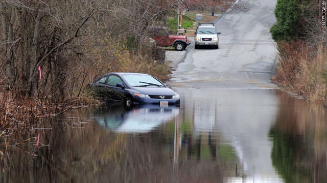 Floodwaters leave a car partially submerged Wednesday in Fall River, Massachusetts, after heavy rainfall in New England.