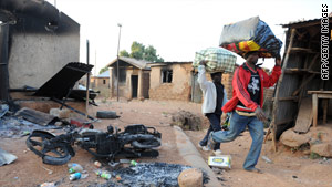 Nigerians flee the city of Kuru Karama on Thursday after religious violence reportedly killed 150 Muslims.