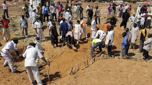 Workers on Saturday close mass graves where dozens of people killed during religious clashes were buried.