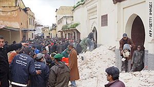 People sift through the rubble of the minaret collapse in Meknes, Morocco, on Friday.