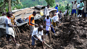Residents of Mbale dig for bodies; the steep terrain has meant heavy machinery could not be used