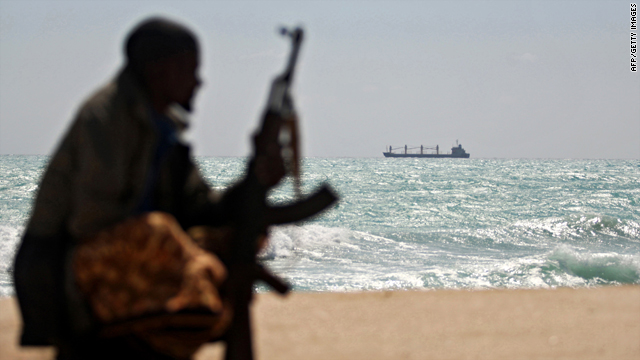 A Somali pirate sits on shore January 7 in northeastern Somalia. Captured Greek vessel the MV Filitsa is in the background.