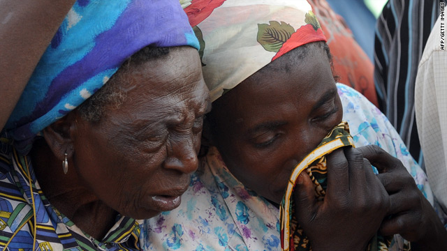 A woman weeps as bodies of massacre victims are cleared away near Jos, Nigeria.