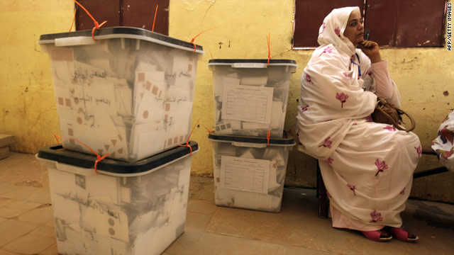 A political party observer sits next to boxes of ballots as polling staff prepare to count votes in Khartoum, Sudan, on Friday.