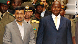 Iranian President Mahmoud Ahmadinejad, left, is welcomed by Uganda's Yoweri Museveni.