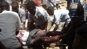 Men evacuate a man wounded Saturday near Bakara market in Mogadishu, Somalia.