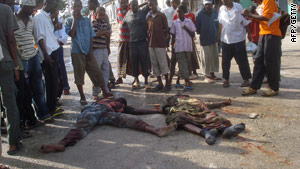 Residents of Mogadishu on Thursday gather around the bodies of two army soldiers killed in clashes with Islamists.