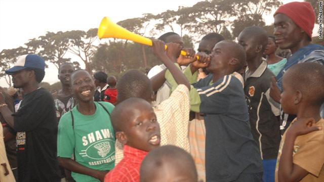 A teen plays a vuvuzela as crowds watch a World Cup screening in Gulu, Uganda.