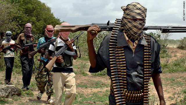 Islamist militia members walk past a training camp in Somalia's lower Shabelle region in October 2009.