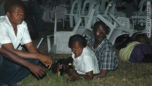 Survivors lie amid overturned furniture after a bombing in a Kampala, Uganda, restaurant on July 11.