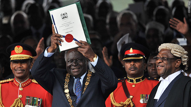 Kenyan president Mwai Kibaki lifts up the new constitution at the Uhuru Park grounds on August 27, 2010 in Nairobi.