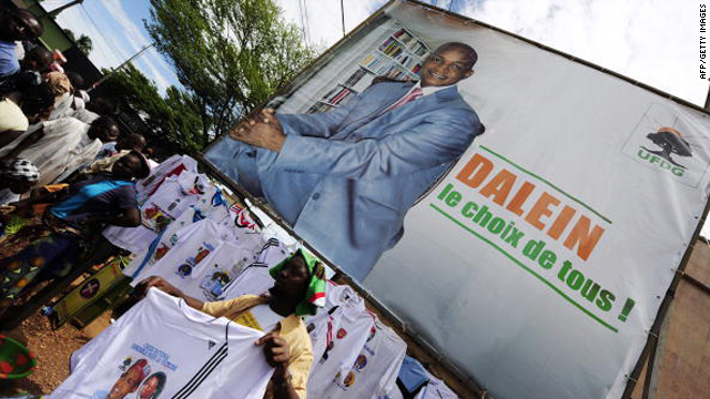 A man sells T-shirts under a giant poster of Guinea's presidential frontrunner Cellou Dalein Diallo on September 18, 2010.