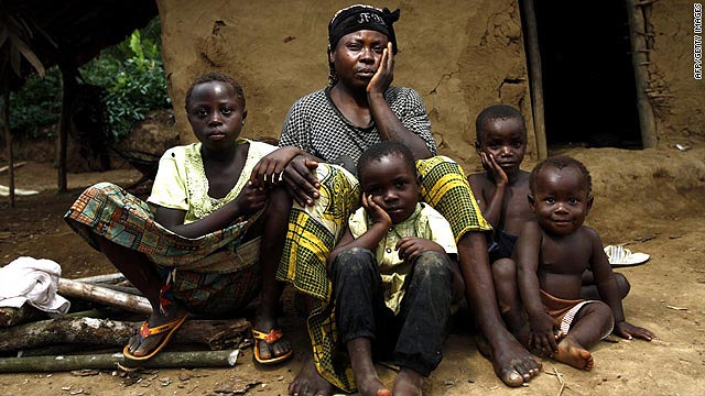 A woman, raped along with her 15-year-old daughter (not pictured) by members of the FDLR, poses with her children.