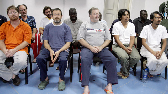 Oil workers taken hostage by Niger Delta militants sit during a press presentation after being released on November 18.