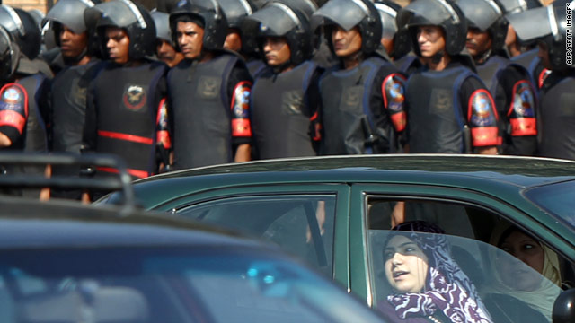 A woman drives past a row of Egyptian riot police near Cairo University campus during a protest by opposition supporters.