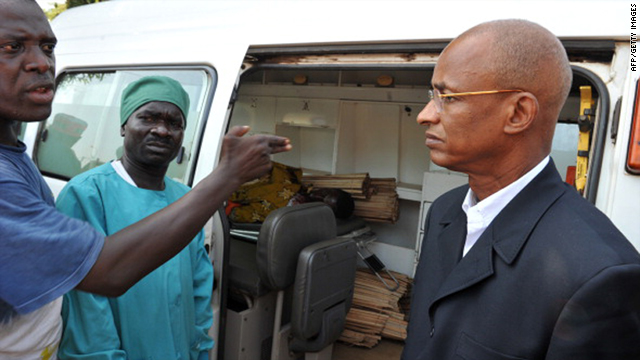 Defeated Guinean presidential candidate Cellou Dalein Diallo, right, stands on November 17, 2010 outside of a van in which lays the body of a man killed by the military in violent protests following presidential elections.