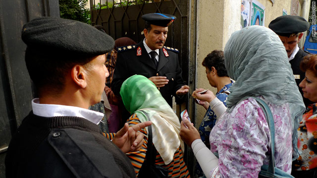 Police check voters' identification at a polling place in Cairo, Egypt, on Sunday.