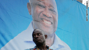 A supporter stands guard in front of President Laurent Gbagbo's campaign headquarters Thursday in Abidjan.