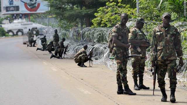 Armed members of the New Forces (FN) adopt combat positions near the hotel that houses the rival government declared by Alassane Ouattara in Abidjan on Monday.