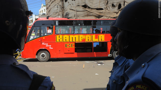 Kenya policemen stand at the scene on December 21 where one person was killed and at least 40 wounded in a bus blast.