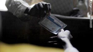 A resident of the Southern Sudan village of Nyal receives his voting card from a referendum worker at a local school.