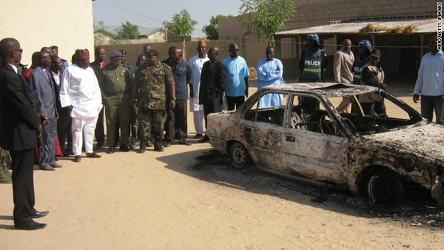 Borno state governor Ali Modu Sherif (in white kaftan) inspect the charred remains of a car outside a Victory Baptist church in Alamderi neighbourhood of the northern Nigerian city of Maiduguri on Saturday.