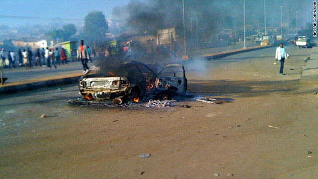 A car burns outside the Nigerian city of Jos following a series of bombings on Christmas Eve.