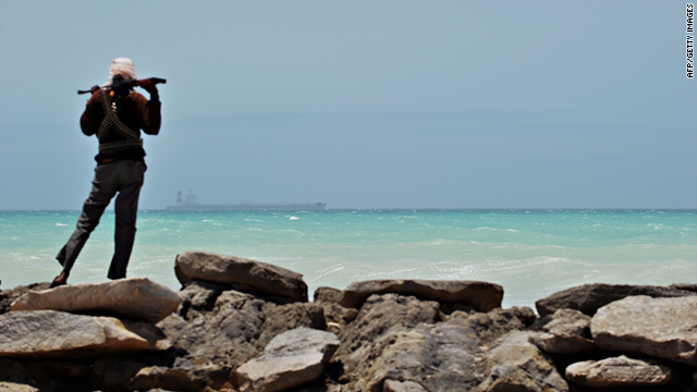 A pirate stands on a rocky outcrop on the coast in Hobyo, central Somalia, on August 20, 2010.