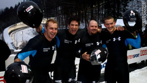 U.S. bobsled pilot Steven Holcomb, second from right, celebrates with teammates after recent bobsled run.