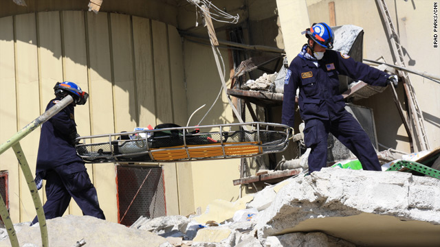 Rescuers carry equipment across the rubble of a grocery store where five people were rescued.