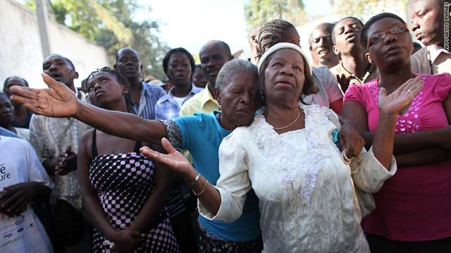 Haitian people pray during Sunday mass outside of the destroyed cathedral of Port-au-Prince, five days after the earthquake.