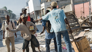 Looters brawl as a man tries to intervene in downtown Port-au-Prince on Monday.