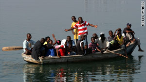 Residents of Port-au-Prince leave the city from a small port area, destination unclear.