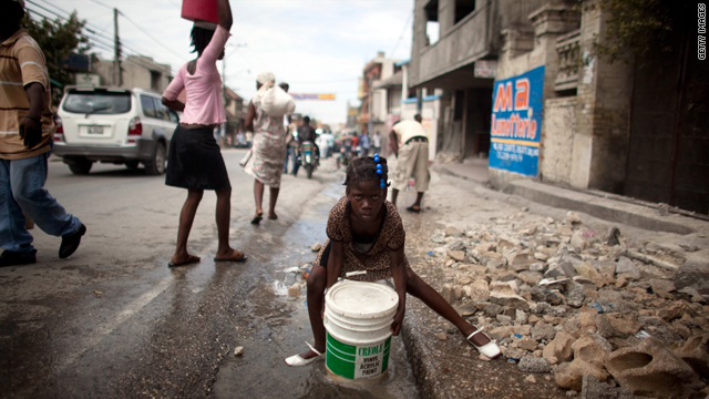 A girl collects water from a broken pipe in the street on January 19, 2010, in the Haitian capital, Port-au-Prince.