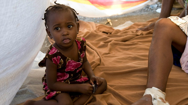 A girl sits by her injured mother in a tent city in Port-au-Prince, Haiti, on Monday.