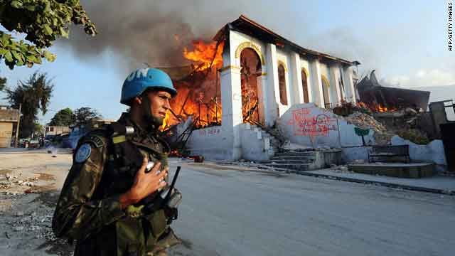 A Brazilian U.N. soldier secures the area around a church that burned Tuesday after collapsing during last week's earthquake.